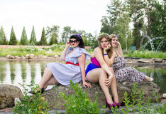 Three beautiful plus size models are sitting near the lake. Three beautiful plus size models are sitting on the shore of the lake,  professional makeup and Royalty Free Stock Photography