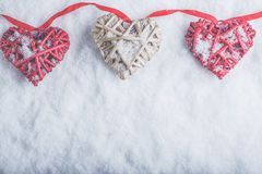 Three beautiful romantic vintage hearts are hanging on a red band on a white snow background. Love and St. Valentines Day concept. Stock Images