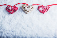 Three beautiful romantic vintage hearts are hanging on a red band on a white snow background. Love and St. Valentines Day concept. Royalty Free Stock Photography