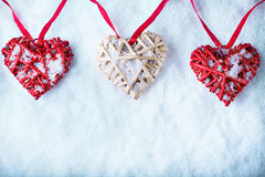 Three  beautiful romantic vintage hearts are hanging on a red band on a white snow background. Love and St. Valentines Day concept Stock Photo