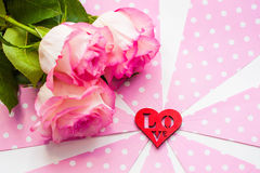 Three beautiful roses and red figure of heart on pink  white background. St. Valentine`s day Stock Image