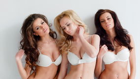 Three beautiful curvaceous young women. Modeling white bras showing off their ample cleavages as they pose arm in arm looking seductively at the camera stock footage
