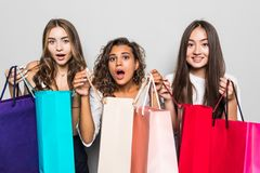 Three beautiful shocked women looking inside shopping bags isolated over gray background. Black friday sales concept. Shopping. Three beautiful shocked women royalty free stock photo