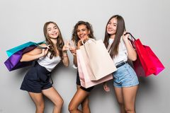 Three beautiful shocked women looking inside shopping bags isolated over gray background. Black friday sales concept. Shopping. Three beautiful shocked women royalty free stock images