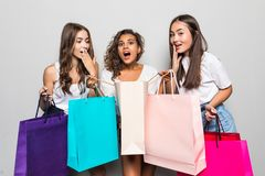 Three beautiful shocked women looking inside shopping bags isolated over gray background. Black friday sales concept. Shopping. Three beautiful shocked women stock photography