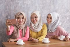 Three beautiful siblings taking selfies together. Portrait of three beautiful siblings taking selfies together at cafe Royalty Free Stock Photos