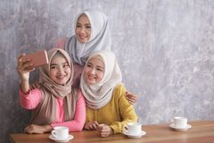 Three beautiful siblings taking selfies together. Portrait of three beautiful siblings taking selfies together at cafe with copy space Stock Images