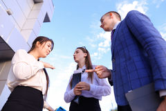 Three beautiful smart young businessman talking, shaking hands,. Two cute successful women and elegant handsome male men successful young office workers Royalty Free Stock Image