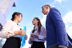 Three beautiful smart young businessman talking, shaking hands,. Two cute successful women and elegant handsome male men successful young office workers Royalty Free Stock Images
