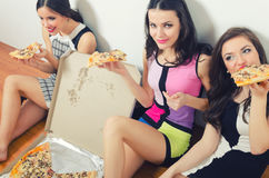 Three beautiful smiling happy fashionable girls eating pizza. After partying and night out Stock Image