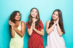Three beautiful smiling mixed race women in summer dresses hugging and looking at camera isolated over green background royalty free stock photo