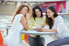 Three beautiful stylish girls sit at a table in a cafe in the modern mall and chat after shopping royalty free stock photos
