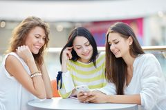 Three beautiful stylish girls sit at a table in a cafe in the modern mall and chat after shopping stock image