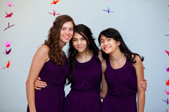 Three beautiful teen girls together in matching pruple dresses Stock Photo