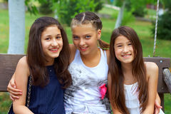 Three beautiful teenage girls in summer park Royalty Free Stock Image