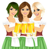 Three beautiful waitresses holding beer mugs for oktoberfest party toasting wearing a dirndl Royalty Free Stock Photo