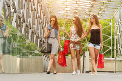 Three beautiful woman on the bridge, hand held shopping bags Royalty Free Stock Photography