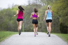Three beautiful woman run in the park Royalty Free Stock Photos