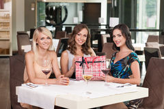 Three beautiful woman sitting at the restaurant. Stock Image