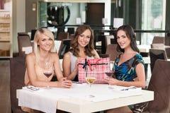 Three beautiful woman sitting at the restaurant. Stock Image