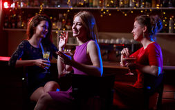 Three beautiful women at bar. Three beautiful young women sitting at bar with drinks Stock Photos