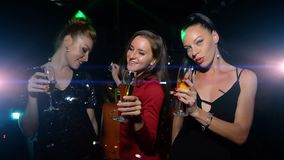 Three women dance, have fun and hold glass of champagne on celebration party