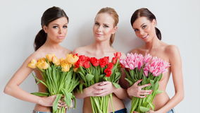 Three beautiful women with fresh spring tulips stock video