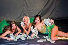 Three  beautiful women lie on money Royalty Free Stock Images