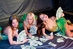 Three  beautiful women lie on money Royalty Free Stock Photo