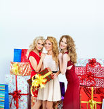 Three beautiful women with a lot of gifts Royalty Free Stock Images