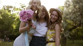 Three beautiful women posing for the camera. Hugging, smiling. Bachelorette concept. Girls having fun together in the. Green park stock footage