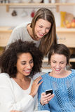 Three beautiful women reading a text message. Three excited beautiful women friends grouped together in the livimg room reading a text message on a mobile phone Stock Photography