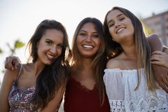 Three beautiful women standing together smiling royalty free stock photo