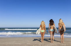 Three Beautiful Women Surfers In Bikinis With Surfboards At Beac Stock Photo