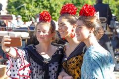 Three Beautiful women taking selfie photo at the Seville`s April Fair.  stock photos