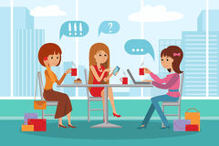Three beautiful women talking at coffee shop while drinking and using phone laptop. Three beautiful friends women with shopping packages talking friendly at Royalty Free Stock Photography