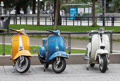 Three beautiful yellow, blue and white retro vespa scooters park Royalty Free Stock Photo