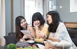 Three beautiful young asian women friends using tablet computer talking smiling and laughing together. At home Royalty Free Stock Images