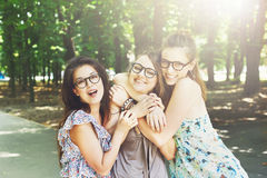Three beautiful young boho chic stylish girls walking in park. Stock Photos