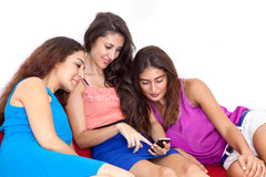 Three beautiful young female friends looking at cell phone. Royalty Free Stock Photos