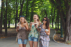 Three beautiful young girls eat donuts in park. Royalty Free Stock Photography