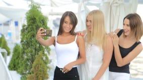 Three beautiful young girls make selfie, girls make a photo using a smartphone. Three beautiful young girls make selfie, girls make a photo stock video footage