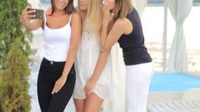 Three beautiful young girls make selfie, girls make a photo using a smartphone. Three beautiful young girls make selfie, girls make a photo stock footage