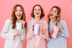 Three beautiful young girls 20s wearing colorful striped pyjamas. Smiling and drinking cold soda from paper cups during happy sleepover isolated over pink Stock Photography