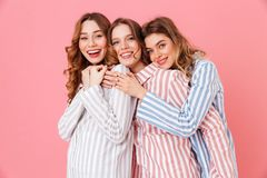 Three beautiful young girls 20s wearing colorful striped pyjamas. Hugging together and having fun during sleepover isolated over pink background Stock Images
