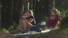 Three beautiful, young girls sitting on the bedspread, on the ground in jeans, sweatshirt, shorts, costume, sneakers stock video