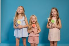 Three beautiful young girls and sweet candy lollipops royalty free stock photography