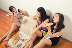 Three beautiful young ladies eating pizza Stock Photo