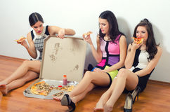 Three beautiful young ladies eating pizza Stock Photos