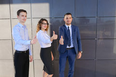 Three beautiful young people showing thumbs up, laughing, smilin Stock Photo